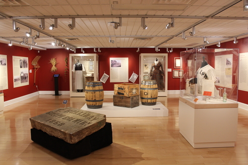 Exhibit installation view of Brewing Changes Guelph. The walls are painted red with various panels and cases around the room. A large cornerstone tablet is on display in the foreground.
