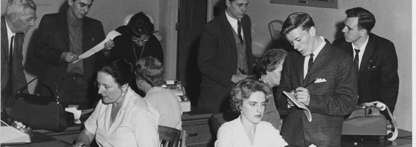 Guelph Mercury Newsroom circa 1960, two women sitting at desks typing, 5 men in suits standing and talking to each other.