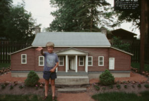 Colour slide of the Priory Model in Riverside Park, with Jonathan Coulman standing in front. The model is made of miniature red logs and has a grey roof. There is a small garden around the model, and a black sign with white writing hanging at the upper right. Jonathan is wearing a blue t-shirt and shorts, and holds out his right arm. In the background is a fence and trees.