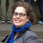 Photo of Dana Weiner, wearing a blue scarf and smiling at the camera.